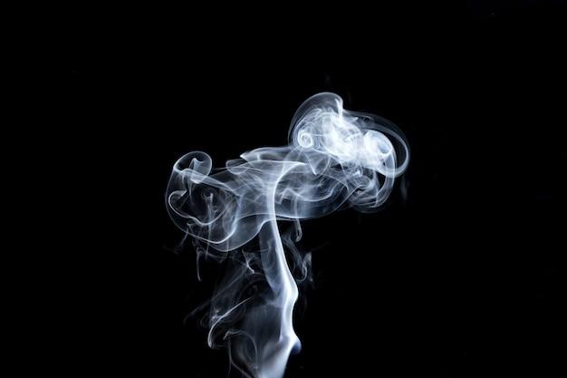 黒に分離された抽象的な白い煙
