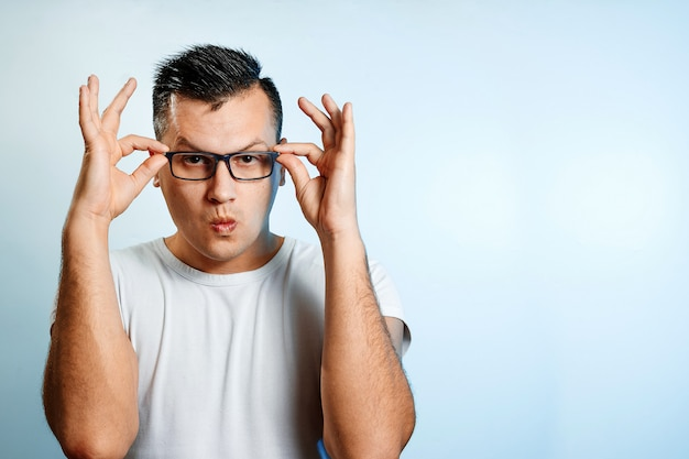 Крупным планом портрет человека, который поправляет очки руками.