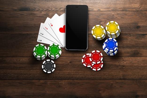 オンラインカジノ、モバイルカジノ、携帯電話の上面図、木材上のチップカード
