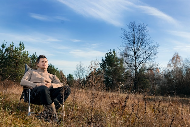 自然の中でロッキングチェアに座っている男