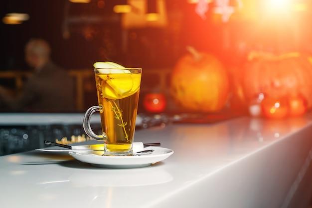 白いバーカウンターの上のガラスのコップにリンゴのスライスと緑茶