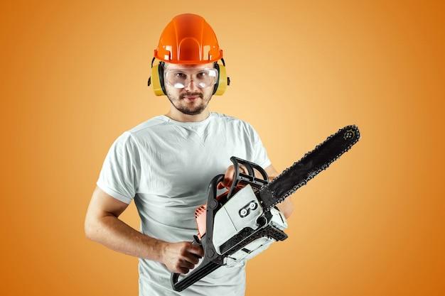 ヘルメットのひげを生やした男はオレンジ色の背景にチェーンソーを保持します。