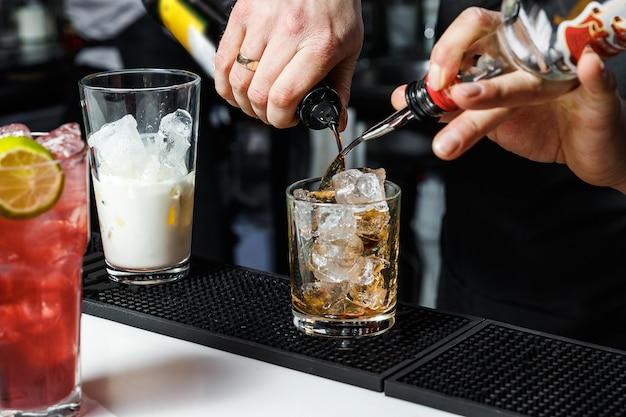 Бармен делает коктейль у барной стойки в ночном клубе