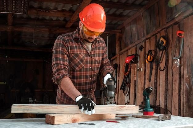 男の大工は、電動ジグソーパズルを使用して男性の手を使用して木製の梁をカットします。