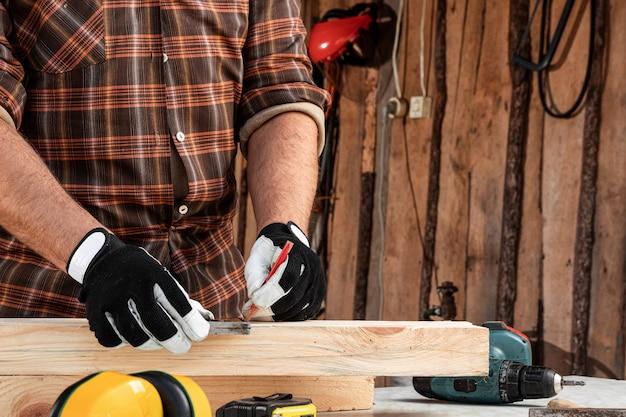 大工の男は、木の板に鉛筆のクローズアップで男性の手を切断するためのボードマークに鉛筆でノートします。木工