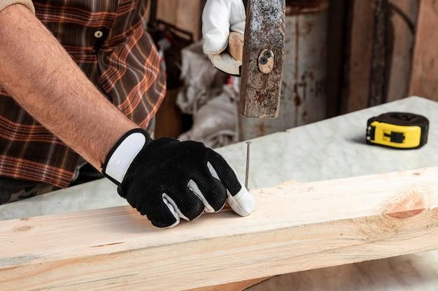 男の大工は、ハンマーのクローズアップで男性の手を木に釘を打ちます。木工