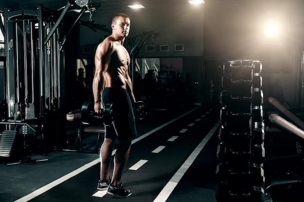 ヨーロッパの外観のハンサムな男、ボディービルダーは、彼の手でダンベルとジムに立っています。スポーツトレーニング、フィットネストレーニング、ジムでのトレーニングの概念。