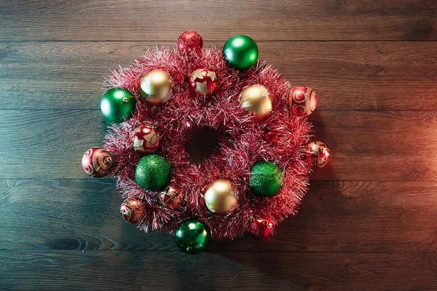 赤い花輪とクリスマスのおもちゃのクリスマスリース、木製のテーブル。メリークリスマスと幸せな休日。上からの眺め。
