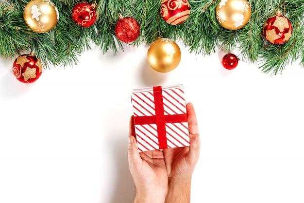 モミ、おもちゃ、ギフト、リボン、白で隔離される赤白のボックスを保持している男性の手の枝。分離します。メリークリスマス、そして、あけましておめでとう。