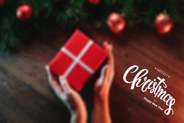 メリークリスマスの碑文、男性の手は木製の茶色のテーブルに贈り物を保持します。クリスマスカード、休日。混合メディア。上からの眺め。