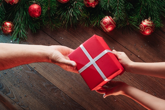 松の枝、クリスマスの飾り、木製のテーブルの上に贈り物をする手のフレーム。メリークリスマスと幸せな休日。上からの眺め。
