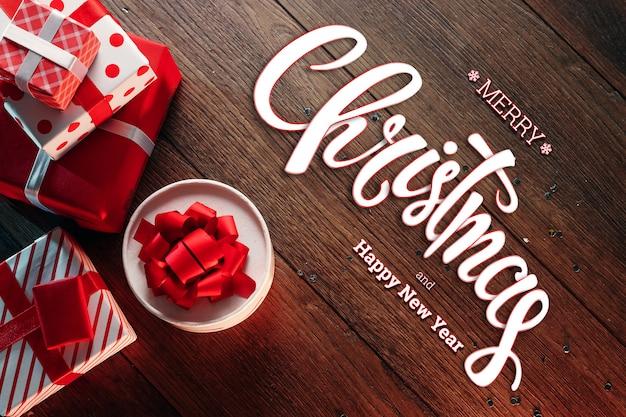 メリークリスマス、装飾、木製の茶色のテーブルの上の贈り物の碑文。クリスマスカード、休日。混合メディア。