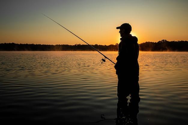 湖の夜明けに男性の漁師が釣り竿をキャッチ