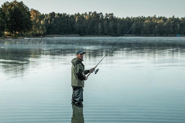 湖の男性漁師が水に立って、釣り竿を釣ります