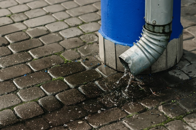 Дождевая вода вытекает из водосточной трубы