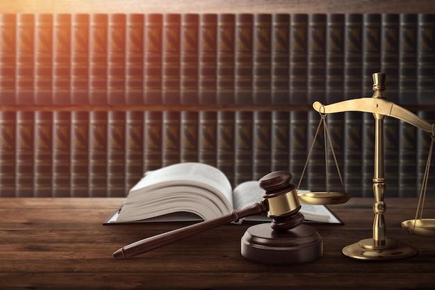 裁判官の小槌と木製のテーブルの上の本