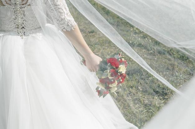 赤と白のバラのウェディングブーケを持って花嫁のクローズアップ。