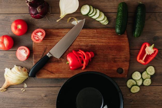 Помидоры черри с ножом, чесноком, перцем и укропом на черном сланце.