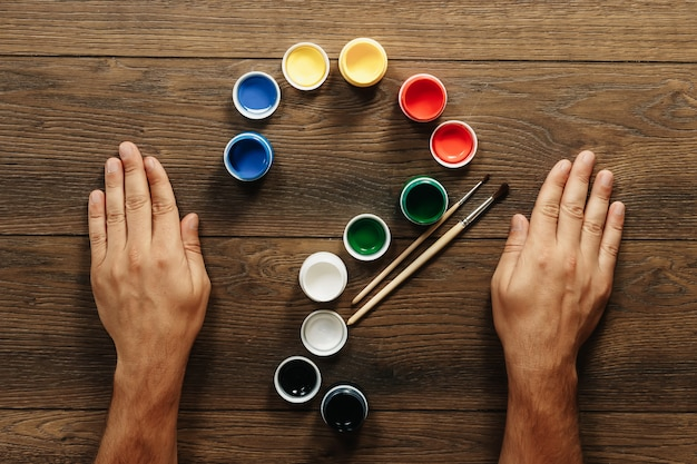 Мужские руки, кисти и открытая краска на коричневом деревянном столе