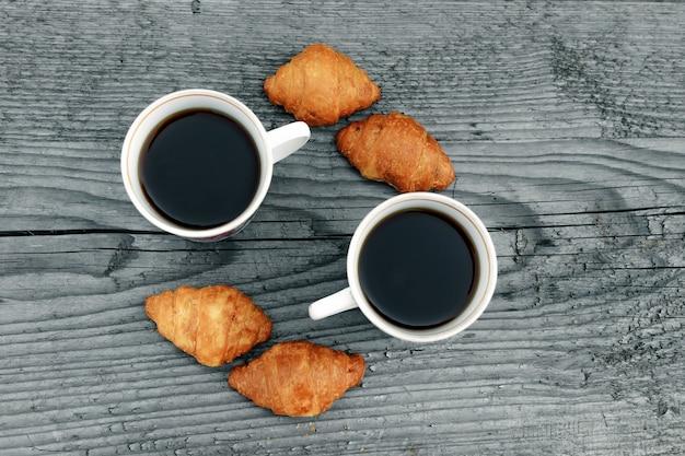 コーヒーカップと木製グレーの焼きたてのクロワッサン。上からの眺め。