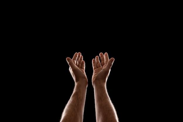黒の背景に分離された男性の手のクローズアップ。
