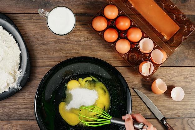 Взбитые яйца. шеф-повар руки крупным планом взбить яйца