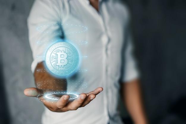 ビジネスマンは、ビットコインアイコン、ビジネス、新技術を手に持っています。