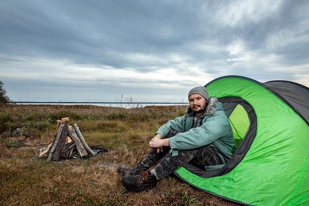 Бородатый мужчина сидит в палатке на фоне природы и озера. путешествия, туризм, кемпинг.