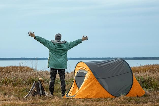 オレンジ色の自然と湖のキャンプテントの近くのひげを生やした男。旅行、観光、キャンプ。