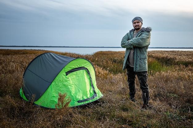 緑の自然と湖のキャンプテントの近くのひげを生やした男。旅行、観光、キャンプ。