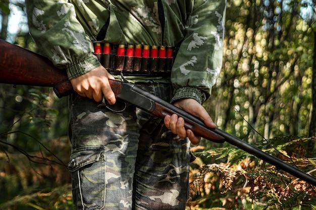 秋の森でハンティング服を着た手に銃を持つハンター