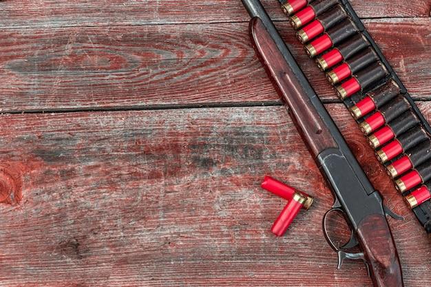 Дробовик и патроны в патронате лежат на деревянном столе