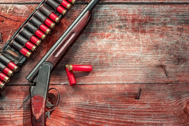 Дробовик и патроны в патронате лежат на деревянном столе, вид сверху