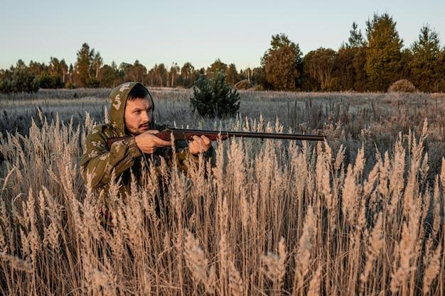 銃を持ったハンターは獲物を待っている草の中に座っています。