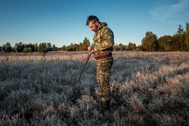 Охотник человек в камуфляже с ружьем во время охоты в поисках диких птиц