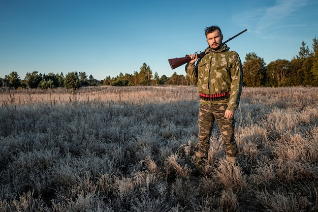 野鳥を探して狩り中に銃でカモフラージュのハンター男