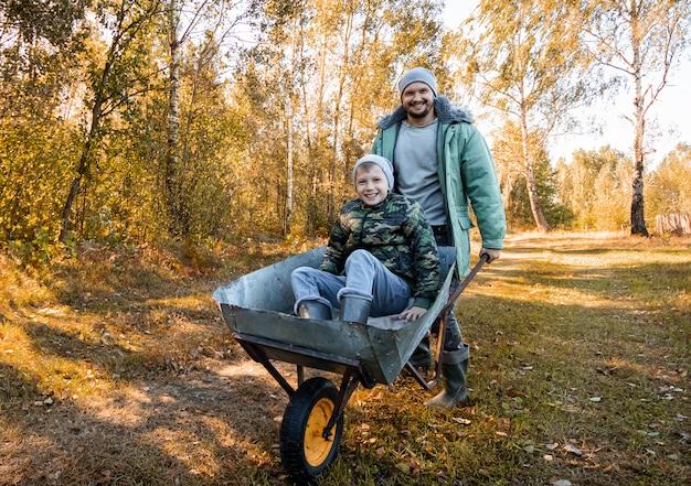 Папа проводит время со своим сыном, счастливым маленьким мальчиком, которого толкает папа