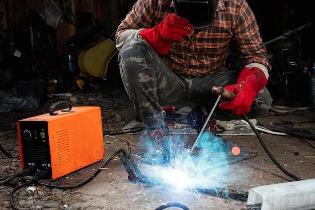Мужской сварщик в сварочной маске работает с дуговым электродом в своем гараже. сварка, строительство, металлообработка.