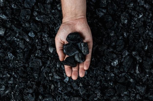 石炭の山の背景に石炭を持つ男性の手、オープンピット採石場での石炭の採掘、コピースペース。