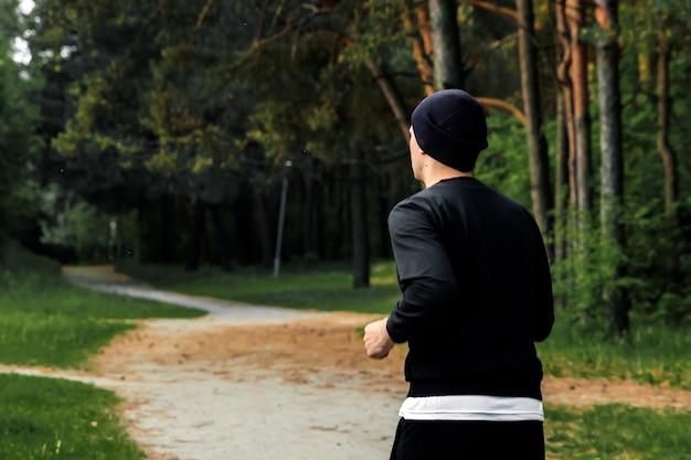 Утренняя пробежка в парке, мужчина в черном спортивном костюме бегает по парку, копирует пространство