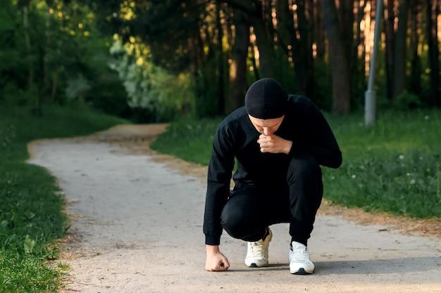 男は夏の朝に緑豊かな公園で朝のトレーニングの準備運動をしています