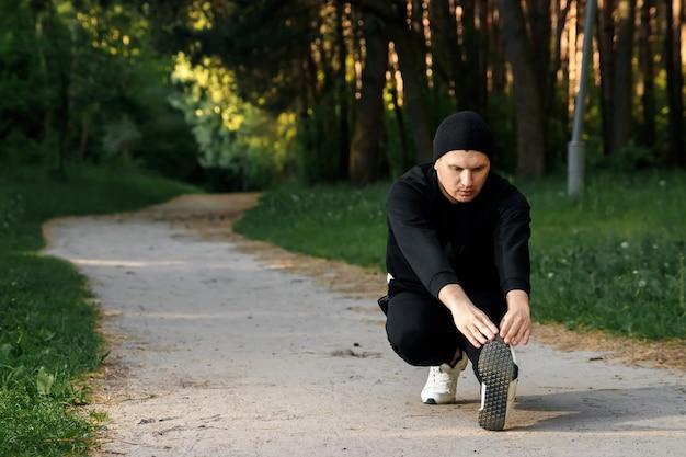 Мужчина делает упражнения, готовится к утренней тренировке в зеленом парке на летнее утро