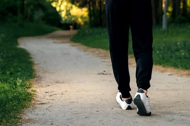 公園での朝のジョギング、男性の足のクローズアップコピースペース