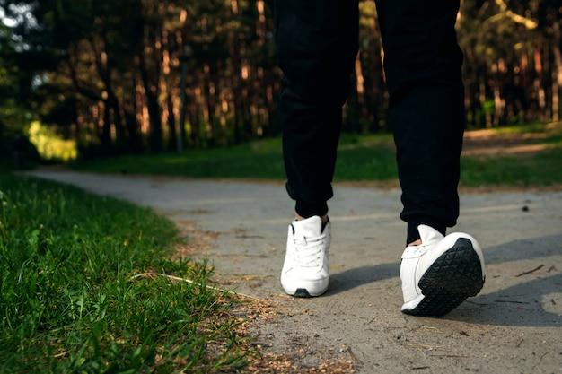 Утренняя пробежка в парке, мужские ноги крупным планом копией пространства