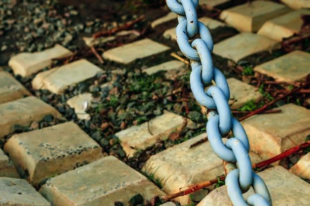 Старая голубая массивная цепь на фоне бетонных плиток
