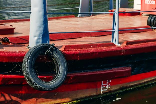 Речной буксир красного цвета, который перевозит по реке