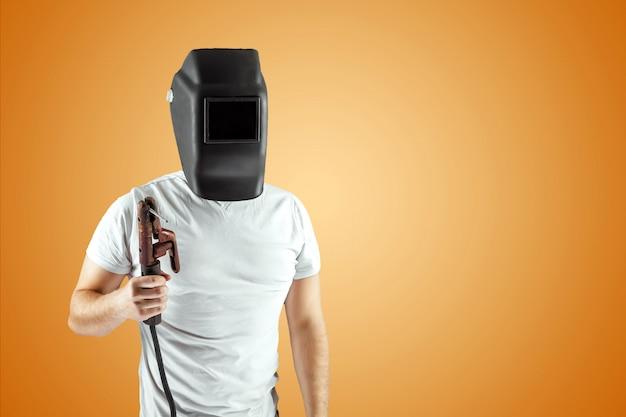 Мужской сварщик в шлеме на оранжевой предпосылке.