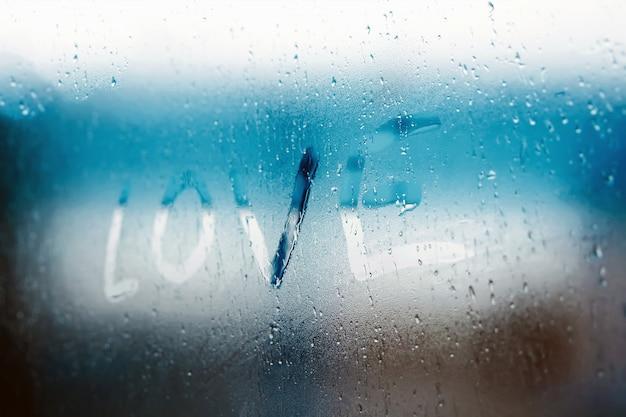 Женская рука рисунок любовь слово на стеклянном окне с концепцией дизайна капли воды