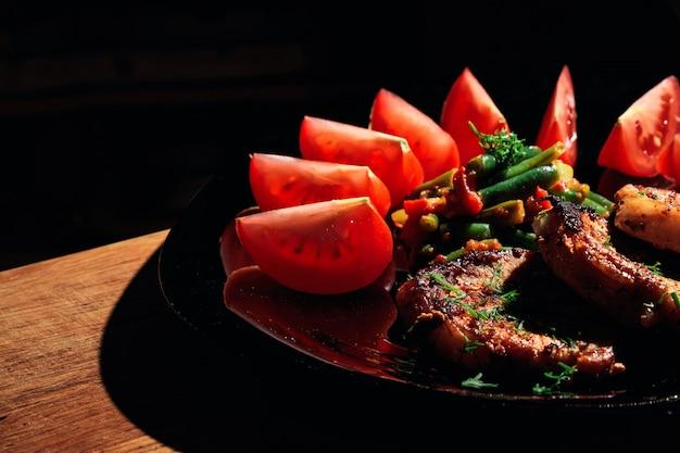 Стейк из свинины на черной тарелке с овощами