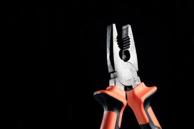 Плоскогубцы, инструмент для ремонта и реновации концепции на черном
